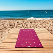 yoga mat on wooden decking overlooking sandy beach and sea