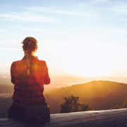 Woman overlooking valley to watch the sun setting