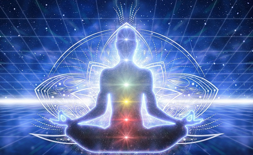 Seated person with chakras shown along spine
